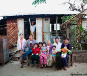 Asian multi-generation family outside shack in Myanmar. Even though it's just a shack, to these people it is home.  There are ten people in the photograph.